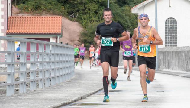 Participantes en la pasada edición del Cross Vuelta al Pantano de Eugi, cruzando la presa en el tramo final.