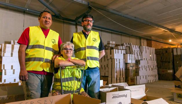 De izda a dcha: Roger Taipe Álvarez, Antonia Linares Garvín y Jesús Denia Medrano organizan cajas de ropa en la bajera de Buztintxuri.