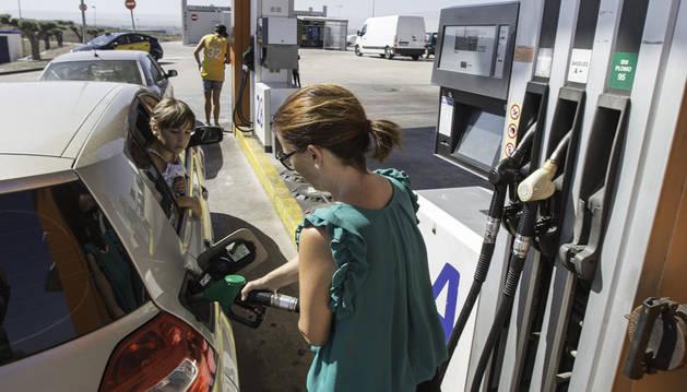 Una mujer reposta en la gasolinera Bardenas ubicada en el polígono industrial La Serna de Tudela.