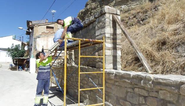 Dos de los trabajadores ultiman la construcción de un muro de piedra en Lodosa.