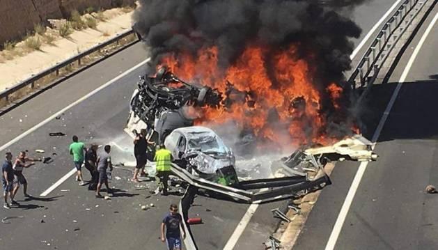 El camión ha quedado volcado encima de uno de los dos turismos y, al menos, uno de estos dos vehículos se ha incendiado.