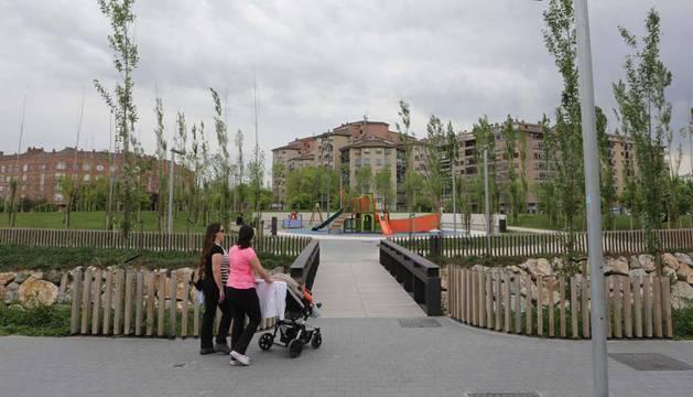 Dos mujeres pasean a un niño en carrito en el parque del orfeón pamplonés.