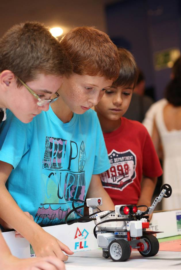 Alumnos participantes en el curso muestran sus robots.