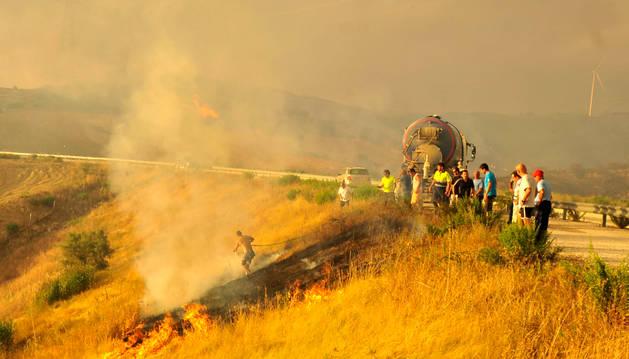 """El ganadero artajonés Iñaki Ganuza, el jueves, sofocó el fuego que saltó el Canal, con la manguera del camión cisterna de Miguel Sola Lorea """"piyayo"""" (tercero por la izda)."""