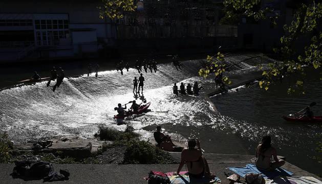 Varias personas toman el sol y se bañan en el río Arga de Pamplona.