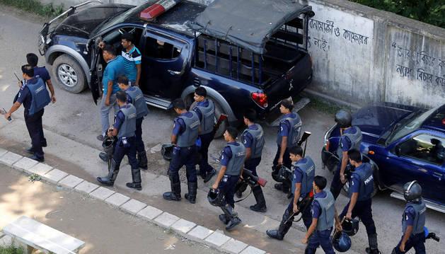 El personal de seguridad a pie por un camino que conduce al sitio de un tiroteo con militantes en las afueras de Dacca.