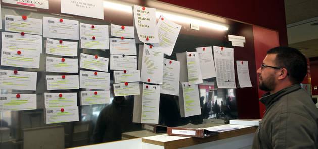 Un hombre mira ofertas de trabajo en una oficina de empleo.