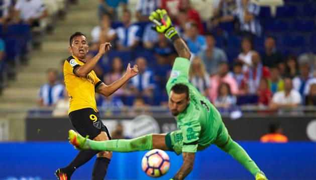 El delantero brasileño del Málaga CF Charles Dias (i) remata frente a Roberto, portero del Málaga, para conseguir el segundo gol del equipo frente al RCD Espanyol
