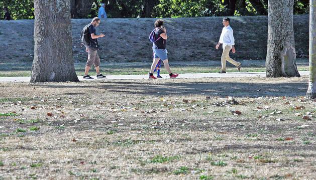 Varias personas pasean por el parque de La Runa, en la Rochapea, donde las zonas verdes han acusado la falta de lluvias y el calor.