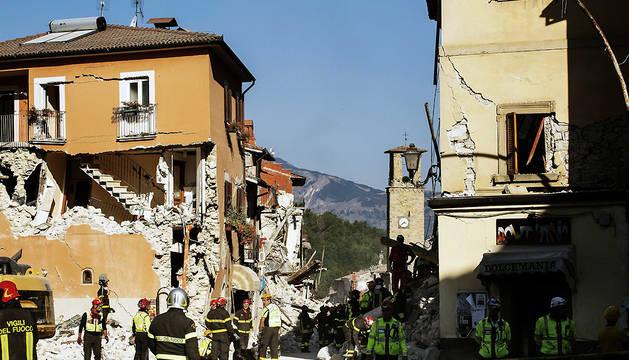 Bomberos trabajan en los restos de edificios dañados por el terremoto en la localidad de Amatrice.