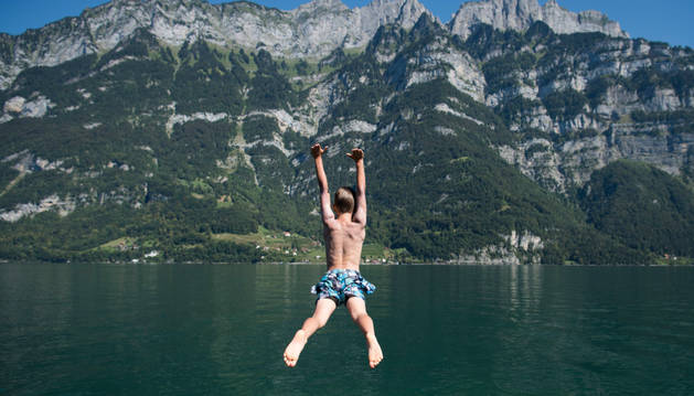Un niño salta en el agua del lago Walensee en Murg , Suiza