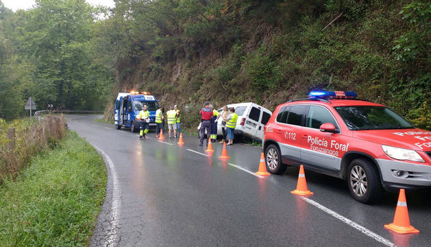 Una patrulla de la Policía Foral y una ambulancia, junto al vehículo accidentado.