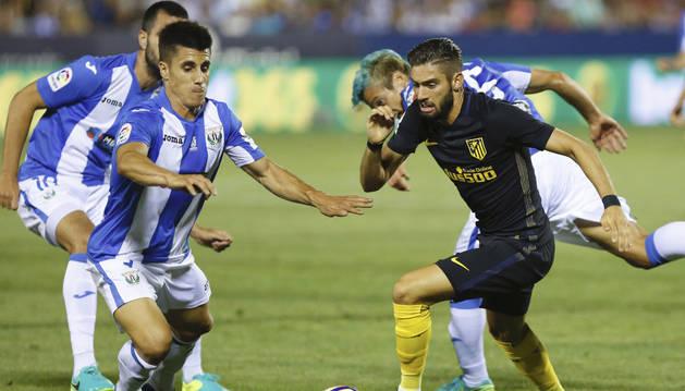 El delantero del At. de Madrid, Yannick Carrasco (d), intenta llevarse el balón ante el defensa del Leganés, Unai Bustinza.
