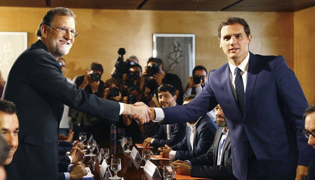 Rajoy y Rivera se estrechan la mano durante la reunión de sus respectivas delegaciones.