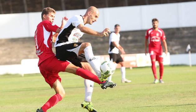 El delantero del Tudelano, Ion Vélez, trata de controlar el balón ante la presión de un jugador del Somozas.