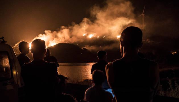 Varias personas observan el fuego, la noche del pasado jueves, en las inmediaciones de la balsa de Artajona.