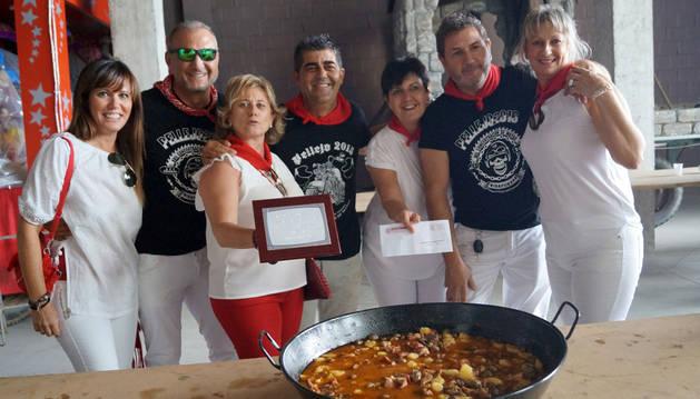 Miembros de la peña El Encierro, con el calderete ganador, la placa conmemorativa y el importe económico.