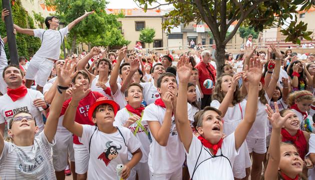 Los niños levantan los brazos para alcanzar los balones y caramelos lanzados desde el balcón de la casa consistorial.