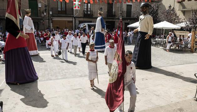 El estandarte local seguido por la corporación municipal, los gaiteros y y la txaranga en su llegada a la iglesia de Santa María de la Asunción de Lumbier.