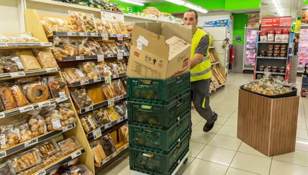 Un empleado de Elkarkide recoge en un supermercado del barrio de Mendebaldea alimentos que se retiran de la venta para donarlos al Banco de Alimentos de Navarra.