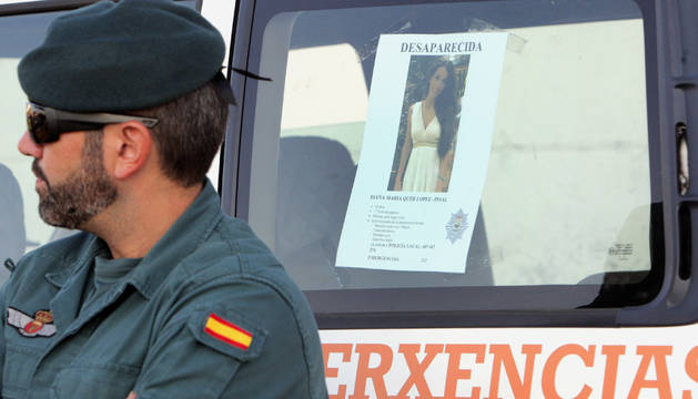 Un efectivo de la Guardia Civil, junto al cartel de la joven Diana Quer, al inicio de la primera batida ciudadana organizada por el Ayuntamiento de A Pobra do Caramiñal.