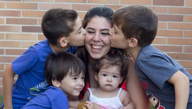 Alicia Urtasun García, recibe un beso de sus mellizos Aimar (dcha) y Unax (izda), de 7 años; mientras sujeta en brazos a la pequeña Amara (8 meses) y Anaitz (3 años) se apoya sobre su pierna, en la terraza de su casa de la Chantr