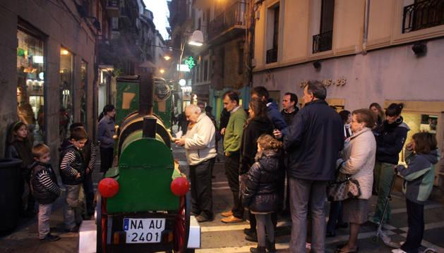 Varias personas hacen cola ante el castañero de la calle Comedias de Pamplona.