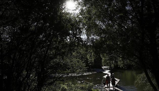 Un grupo de personas atraviesan unas pasarelas sobre el rio Arga bajo un intenso sol.