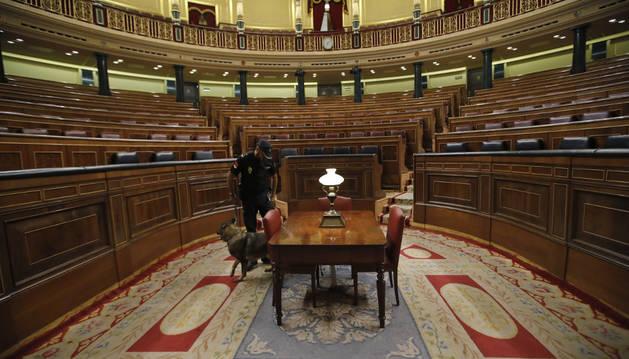 Un agente de la policía registra el hemiciclo del Congreso de los Diputados antes del comienzo de la segunda votación para la investidura del candidato popular, Mariano Rajoy.