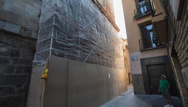 Un vecino mira el andamio ante la Puerta del Juicio para realizar el estudio previo de la restauración.