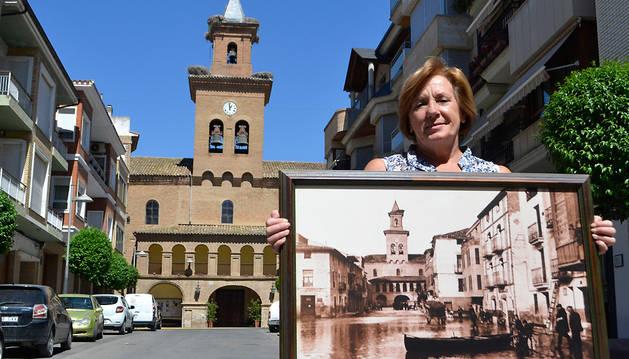 Mari Carmen Moreno Luri en la plaza de los Fueros, delante de la parroquia del Salvador, con la imagen que capturaron en la riada de la Nochevieja y el Año Nuevo de 190 y 1961.