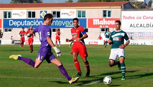 Mikel Pagola trata de despejar el balón ante la oposición de un rival.