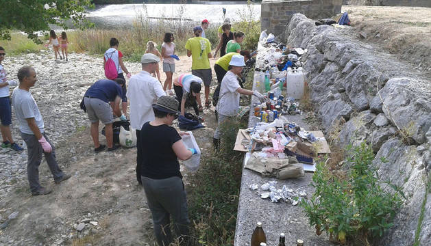 Varios voluntarios recogen basura en el río Arga.