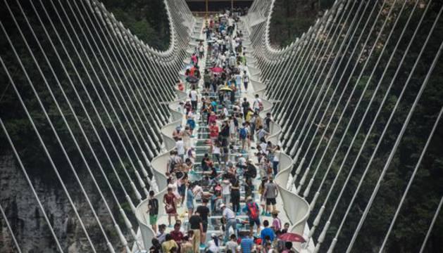 Visitantes recorriendo el puente de cristal.