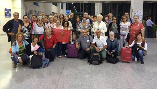 Grupo de voluntarios navarros, con el arzobispo Francisco Pérez, ayer en el aeropuerto de Noáin.