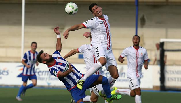 Salto acrobático de Pito, delantero del Izarra, con un jugador rival ayer en el estadio de Merkatondoa donde el cuadro navarro consiguió un valioso punto ante la Cultural.