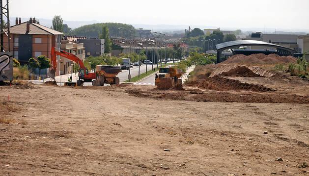 Dos máquinas trabajan en el terreno donde estará el nuevo vial, con las piscinas cubiertas a la derecha de la imagen.