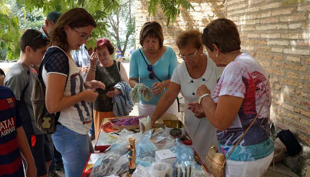 EN EL YUGO... Varias personas recogen los lazos bendecidos de la Virgen del Yugo.