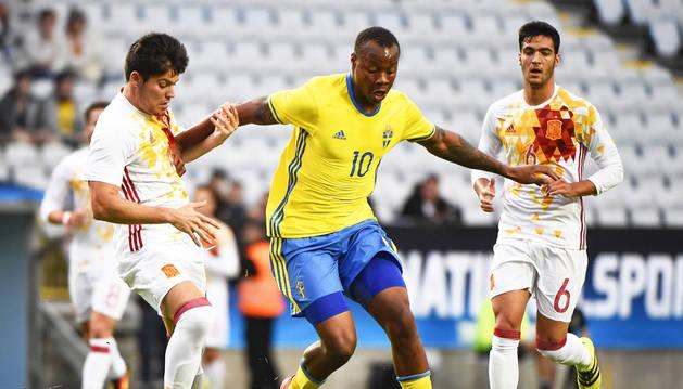 Carlos Strandberg  lucha por el balón ante los españoles, el central Jorge Meré y el centrocampista Mikel Merino.