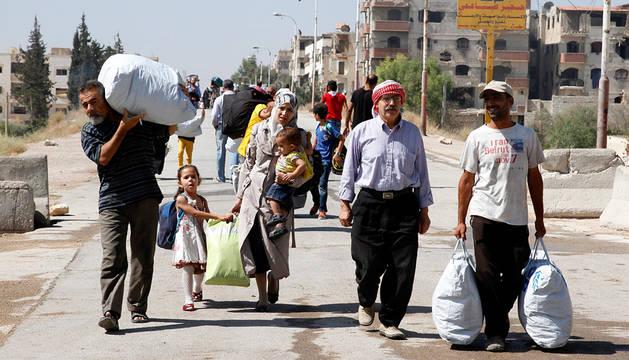 Familias sirias caminan con sus pertenencias al ser evacuados de la ciudad de Maadamiyet al Sham en Siria.