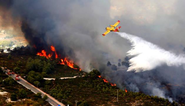 Un hidroavión trata de extinguir el incendio en una de las zonas residenciales de Jávea, Alicante.