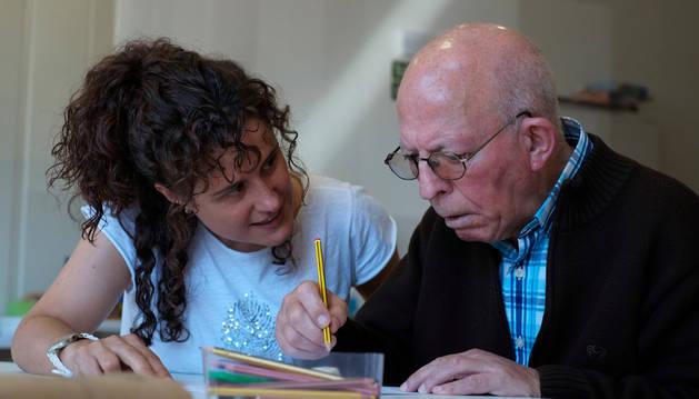 La psicóloga Arantxa Saigós Arístegui, de 40 años, ayuda a Joseba Koldo Martínez-Barranco Pérez, vecino de Leitza y de 82, a completar un ficha para potenciar la memoria, ayer, en el centro de día de Lekunberri.