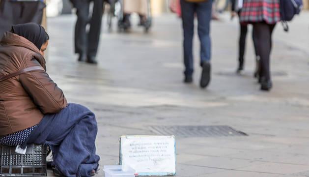 Una persona pide limosna en la calle.