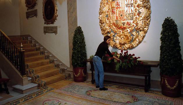 Una persona repasa los centros de flores instalados en el zaguán del Ayuntamiento de Pamplona.