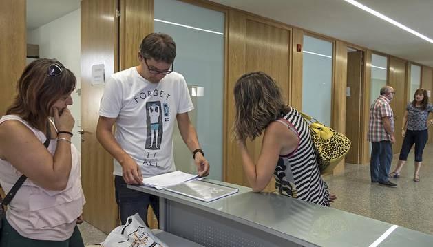 Javier Martínez Giralda atiende a dos personas en el interior de la escuela de música.