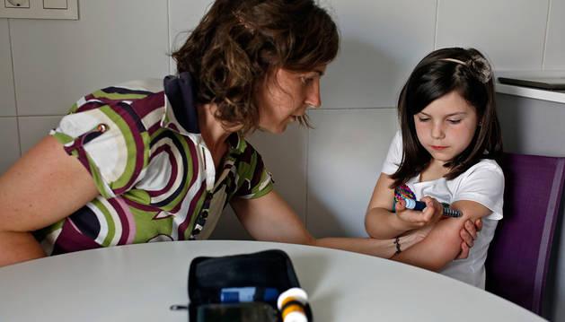 Una niña afectada de diabetes tipo I se inyecta insulina con la ayuda de su madre.