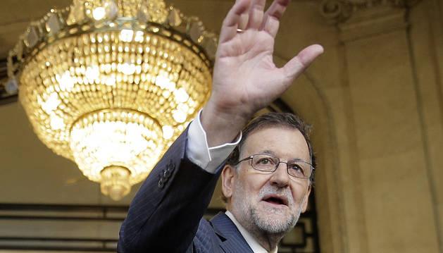 El jefe del Ejecutivo en funciones y líder del PP, Mariano Rajoy, saluda a su llegada esta mañana al Hotel Palace.
