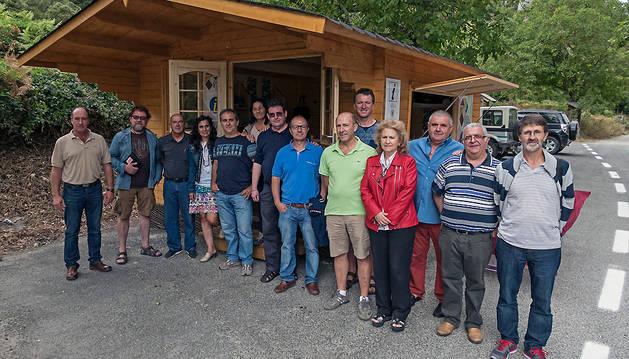 Varios representantes locales delante de una de las casetas de madera.
