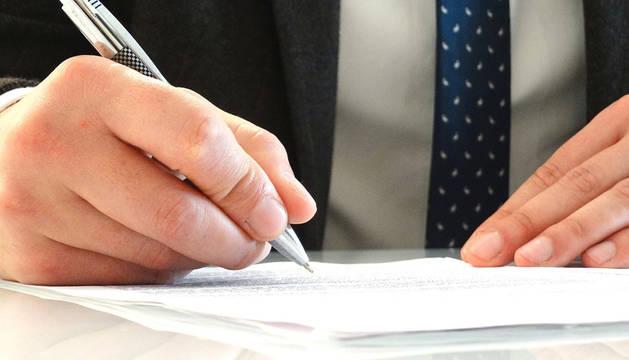Imagen de un abogado firmando documentos.