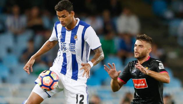El jugador de la Real Sociedad, Willian, lucha un balón con, David López, del Espanyol, durante el partido.